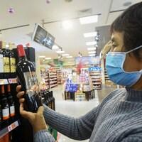 Une femme tient une bouteille de vin.