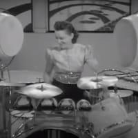 Une femme distinguée joue de la batterie.
