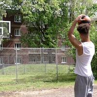Un jeune homme, de dos, s'apprête à lancer un ballon de basketball dans un panier.