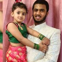 Le grand frère Prithwiraj porte sa petite soeur Anvi Rajkumar dans ses bras. Vêtus de costumes traditionnels, ils fixent la caméra en souriant .