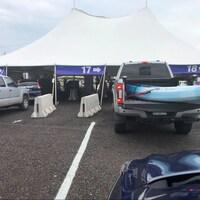 Des voitures et des camionnettes passent sous une grande tente au point de contrôle.