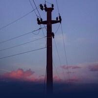 Un poteau de câbles sur fond de coucher de soleil