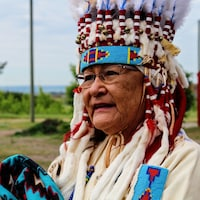 Vivian Ayoungman en habit traditionnel devant le collège communautaire Old Sun.