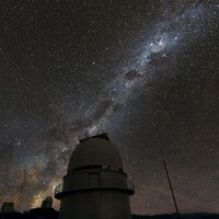 On voit le ciel étoilé et un observatoire au sol.