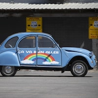 Une voiture ornée d'un arc-en-ciel et du message «Ça va bien aller».