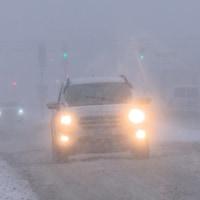 Une voiture aux phares allumés roule sur une route enneigée alors qu'il neige tout autour.