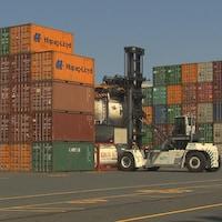 Plusieurs conteneurs de marchandises empilés dans le port de Montréal.