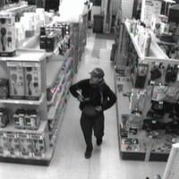 Une capture vidéo montre un homme dissimulant des objets dans un sac