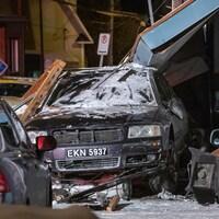 Un véhicule noir sous un balcon effondré, dans la nuit.