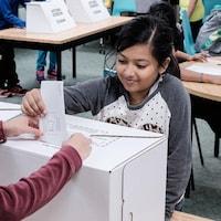Deux fillettes devant une urne de vote