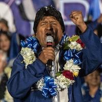 M. Morales, un collier fleuri autour du cou, lève le poing devant la foule.