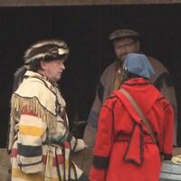 Trois personnes en costume historique parlent.
