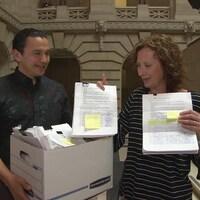 Un homme, Wab Kinew, tient une boite pleine de papiers, et une femme à ses côtés, Jodie Kehl, montre des pages de pétition portant des signatures. Ils sont tous deux dans le hall du Palais légslatif du Manitoba.
