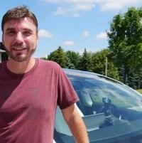 Wade Anderson à Woodstock, en Ontario, après 16 jours de voyage, devant sa voiture. Il a les cheveux châtains, une courte barbe, il porte un chandail bordeau