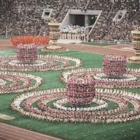 Des centaines de figurants forment quatre pyramides humaines au centre du stade.