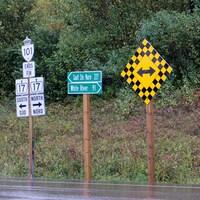Une pancarte indique que Sault-Ste-Marie se trouve à 227 kilomètres. White River à 91.