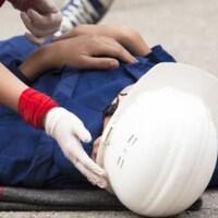 Un travailleur blessé gît au sol.