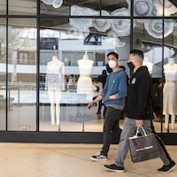Deux clients marchent devant un magasin de vêtements. Ils portent chacun un masque sur le visage.