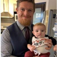 Un homme tenant un bébé dans les bras.