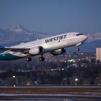 Un avion WestJet s'envole devant les montagnes Rocheuses.