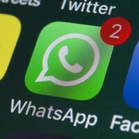 Une photo d'un écran de téléphone sur lequel apparaissent différentes icônes de réseaux sociaux. L'icône de WhatsApp est mise en évidence, au centre, avec une bulle rouge indiquant deux notifications.