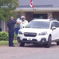 Un véhicule des services médicaux stationné devant le centre de soins. Un homme habillé en habit de protection blanc et portant une visière et un masque respiratoire parle à un agent de sécurité en uniforme.