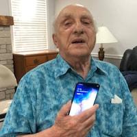 Un vieil homme portant une chemise bleue avec son téléphone cellulaire en main.