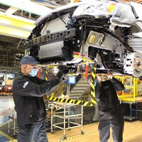 Deux ouvriers travaillent sous une fourgonnette Dodge Caravan dans une usine.