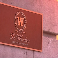 Une plaque sur le mur d'un bâtiment sur laquelle il est écrit: «Le Windsor, salles de bal»