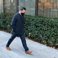 Winston Yep, masqué, marche sur le trottoir.
