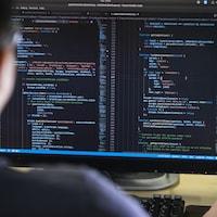 Un homme écrit des lignes de code sur un ordinateur.