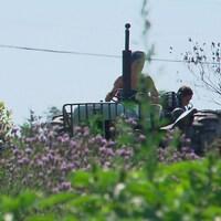 Des travailleurs dans un champs avec un tracteur.