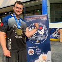 Un homme portant une médaille d'or au cou pose devant l'affiche des championnats du monde de tir au poignet d'Edmonton.