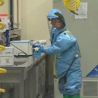 Plan large de Xiangguo Qiu en tenue de protection au laboratoire national de microbiologie de Winnipeg.