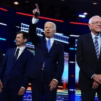Andrew Yang, Pete Buttigieg, Joe Biden et Bernie Sanders sourient.
