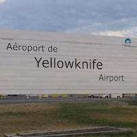 Une pancarte affichant l'aéroport de Yellowknife, avec en arrière-plan la tour de contrôle.