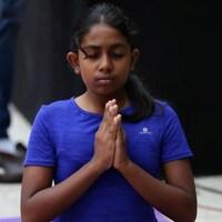 Une jeune fille suit un cours de yoga, à Bangalore.