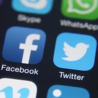 Les icônes des applications YouTube, Facebook et Twitter sur l'écran d'un téléphone mobile