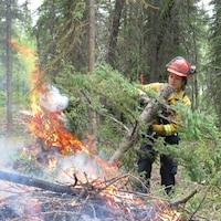 Une pompière dirige un tronçon d'arbre dans un feu.