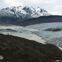 Photo prise du sol du pied du glacier Llewellyn avec de gros morceaux qui flottent devant.
