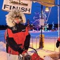 Une femmes sur une traîneau à chiens. Elle est beaucoup habillée. Il y a du gel sur son écharpe. Derrière elle, il y a une banderole sur laquelle il est indiqué : Yukon Quest Finish. Il fait nuit. À droite, une personne est de dos. Elle porte un gilet fluorescent.