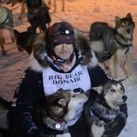 Un homme sur la neige en compagnie de ses chiens de traîneau.