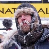 Gros plan sur la tête d'un homme qui porte un gros manteau d'hiver et une capuche. Sa moustache est entièrement gelée.