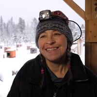 Une femme sourit. Elle porte une tuque en laine avec une lampe frontale dessus. Derrière, on voit un paysage enneigé avec des niches pour chiens.