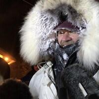 Gros plan d'un homme enveloppé dans un manteau d'hiver avec capuchon et foulard et chapeau. Seuls son nez, ses yeux et sa bouche ne sont pas couverts. Il y a de la neige sur la fourrure de son capuchon et sur ses sourcils. C'est le soir. Plusieurs microphones sont pointés vers lui.