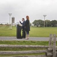 Plan large de M. Blanchet s'adressant aux journalistes derrière une clôture de bois.