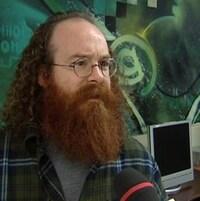 Yves Séguin en entrevue devant des ordinateurs dans un local.
