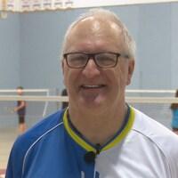 Il sourit à la caméra dans un gymnase où des jeunes jouent au badminton.