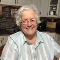 Une femme souriante avec lunettes et cheveux blancs pose dans sa cuisine.