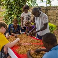 Des personnes autour d'une table enlèvent la coquille d'arachides.